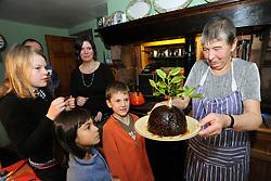 Family serve traditional Christmas pudding