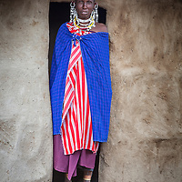 A Masaai mother poses in the doorway of her hut. Since the passing of her husband she now takes care of the entire family herself.