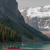 Canoeists paddle rented boats on Lake Louise in Banff National Park, Alberta, Canada.