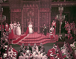 28/10/1958. Queen Elizabeth II, watched by the Duke of Edinburgh, reads her speech from the Throne in the House of Lords chamber at the State Opening of Parliament. The Royal couple will celebrate their platinum wedding anniversary on November 20.