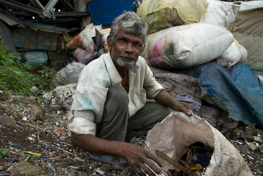 Noting goes to waste in Dharavi. A man collects small pieces of garbage that he will later sell to the plastic recyclers.
