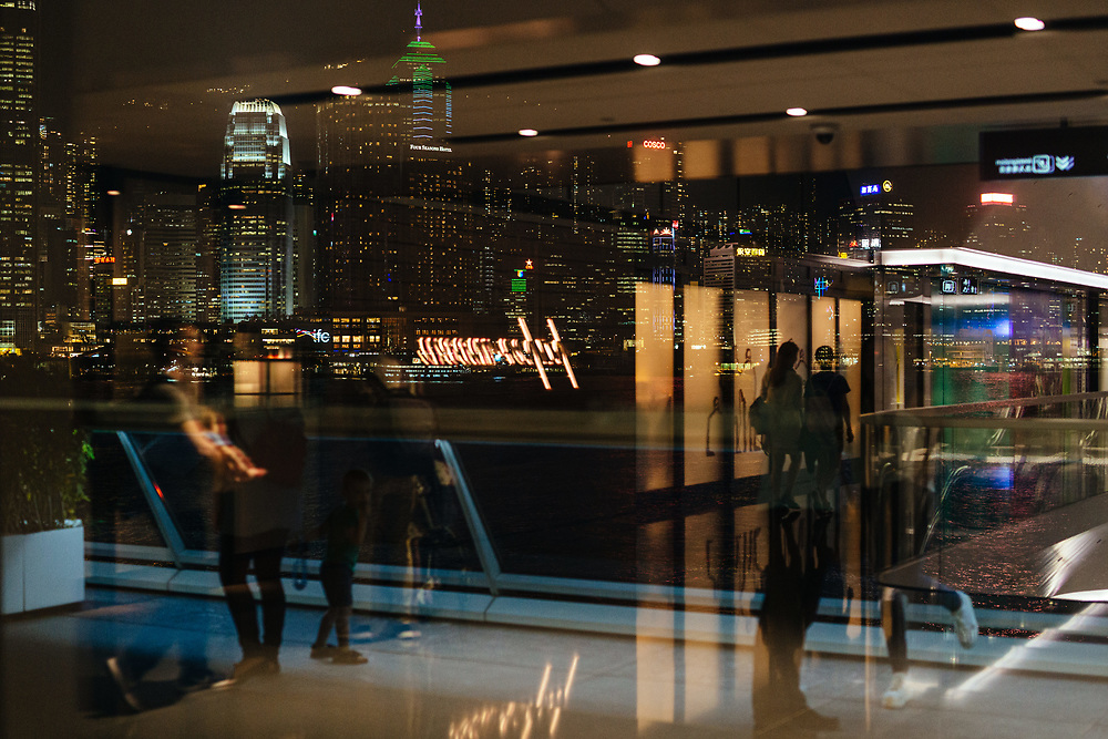 The Hong Kong Island skyline and people are reflected in a window at the Harbour City shopping mall, in Tsim Sha Tsui, Kowloon, Hong Kong, China, on September 25, 2019.