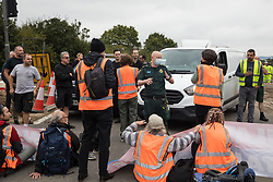 Enfield, UK. 15th September, 2021. An ambulance driver asks Insulate Britain climate activists to move out of a slip road from the M25 at Junction 25 which they were blocking as part of a campaign intended to push the UK government to make significant legislative change to start lowering emissions. The activists, who wrote to Prime Minister Boris Johnson on 13th August, are demanding that the government immediately promises both to fully fund and ensure the insulation of all social housing in Britain by 2025 and to produce within four months a legally binding national plan to fully fund and ensure the full low-energy and low-carbon whole-house retrofit, with no externalised costs, of all homes in Britain by 2030 as part of a just transition to full decarbonisation of all parts of society and the economy.