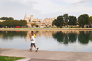 The Pope's palace in Avignon from across the river reflected in the water. A couple running. Avignon, Vaucluse, Provence, Alpes Cote d Azur, France, Europe