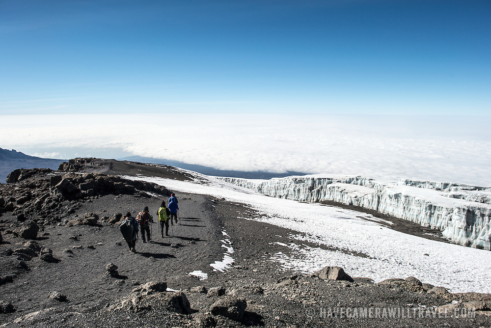 A group of climbers begin the descent from the summit of Mt Kilimanjaro, with permanent glaciers to their right.