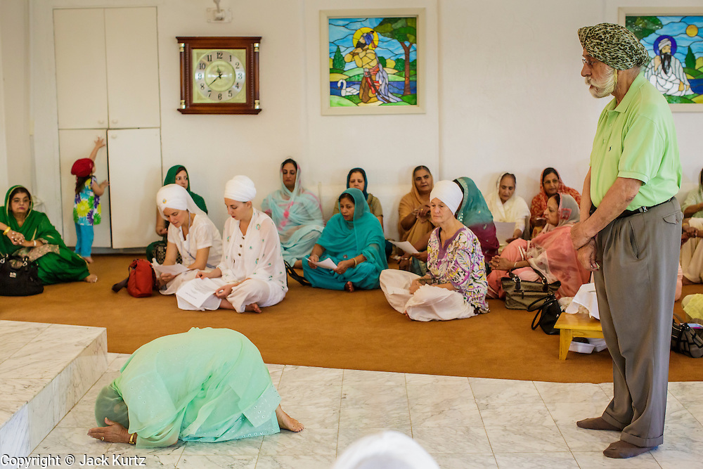 12 AUGUST 2012 - PHOENIX, AZ:  Members of the Phoenix Sikh community enter the Gurdwara to make an offering to the Guru during Sunday services at the Guru Nank Dwara Ashram Sikh temple in central Phoenix. Guru Nank Dwara Ashram is the oldest of three Sikh temples in the Phoenix area. There are about 1,500 Sikh families in the area. Memorials have been held throughout the week to honor the Sikhs killed in the mass shooting in Wisconsin last week. Sunday's service included several mentions of the massacre and was attended by a number of people active in the Phoenix interfaith community.   PHOTO BY JACK KURTZ