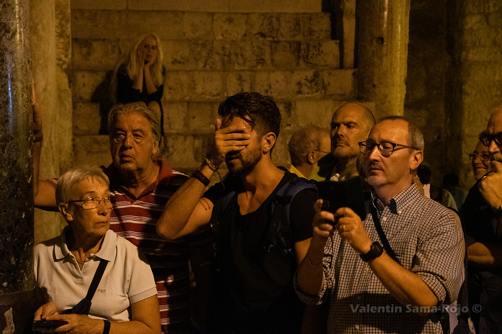 Jerusalem, Israel. 30th August, 2019. People watching and taking pictures while others are praying during the ceremony of closing the doors of the Church of the Holy Sepulchre. © Valentin Sama-Rojo