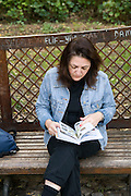 Turkey, Istanbul, Topkapi Palace, Gulhane Park female tourist consulting her guide book Model Release available