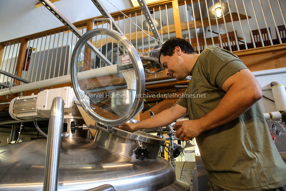 (7/10/19, HOPKINTON, MA) Brewer Chris Locke looks into pone of the tanks at Start Line Brewing in Hopkinton on Wednesday. [Daily News and Wicked Local Photo/Dan Holmes]
