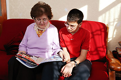 Grandmother and grandson at home reading a magazine together,