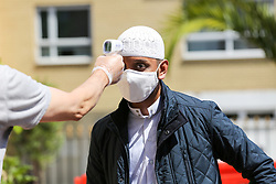 © Licensed to London News Pictures. 20/07/2020. London, UK. A worshipper wearing a face covering has his temperature checked at Wightman Road Mosque, also known as London Islamic Cultural Society and Mosque, in north London as the Mosque reopens for Zuhr (the afternoon prayer) after almost four months of lockdown. Last month the government announced that gatherings of more than 30 worshippers are allowed for acts of communal worship in churches, synagogues, mosques, temples and other places of worship. All worshippers attending Mosques have to wear face coverings and bring their own prayer mat, Quran, and a reusable shoe bag. Photo credit: Dinendra Haria/LNP