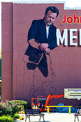 Seymour Indiana - A store named This Old Guitar has a partially completed image of John Mellencamp on its brick side facing the parking lot.
