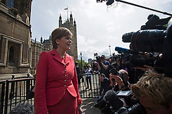 © London News Pictures. 11/05/2015. Leader of the SNP Nicola Sturgeon surrounded by media as she is greeted by 56 SNP Members of Parliament outside the St Stephens Entrance to the Houses of Parliament  as they arrive at Westminster following their election sucess. Photo credit: Ben Cawthra/LNP