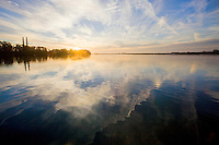 Sunset illuminates the calm waters of Elkhorn Slough in Moss Landing, California.