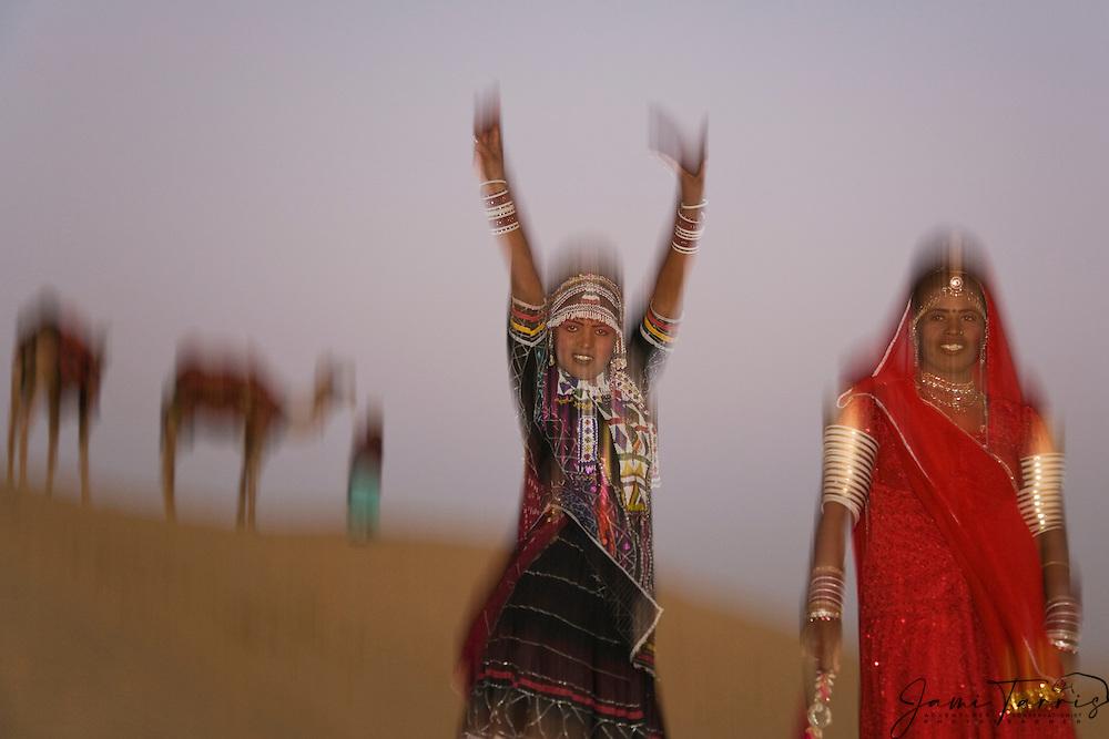 Motion-blur of two tribal girls in the That Desert dancing and teasing, Thar Desert, Rajasthan, India