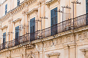 Goose breast ironwork balcony of ornate building in Largo Lamdolina in Noto city, Sicily, Italy