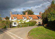 Rain storm clouds over pretty attractive cottages in village of Blaxhall, Suffolk, England, UK