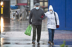 © Licensed to London News Pictures 03/01/2021.        Sidcup, UK. A couple wearing protective masks in the High Street. Heavy rain in Sidcup, South East London this Sunday afternoon as a weather warning has been issued for a -12C Arctic chill in the UK. Photo credit:Grant Falvey/LNP