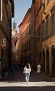 A narrow street leading to the Piazza del Campo, early in the morning in Siena, Tuscany, Italy
