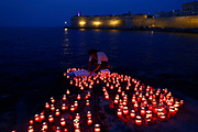 A man places candles during a vigil to remember migrants who have lost their lives whilst crossing the Mediterranean, and to insist that such loss of life is never normalised in light of some European governments enacting policies which are preventing NGO rescue ships from operating, in Valletta's Marsamxett Harbour, Malta July 5, 2018.  REUTERS/Darrin Zammit Lupi