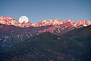 The full moon setting over the Olympic Mountains Northeast part of the mountain range including Boulder Ridge, The Needles, Buckhorn Mountain and Iron Mountain with morning alpenglow coloring the peaks and snow as viewed from the Kitsap Peninsula, to the east, Olympic National Park and National Forest.  Washington, USA.