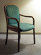 three quarter view of an empty chair in a motel room