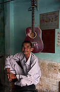 Portrait of a store owner with guitar, Saigon.