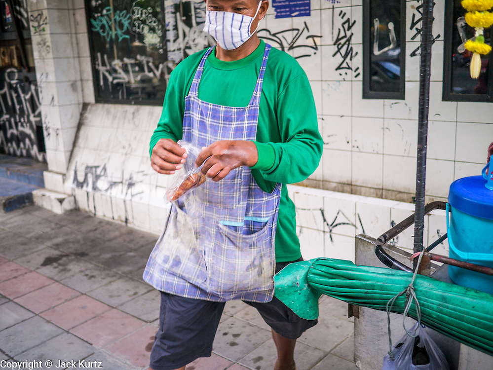 """04 OCTOBER 2012 - BANGKOK, THAILAND:  A grilled meat vendor takes a """"to go"""" order to a waiting taxi driver on Sukhumvit Road in Bangkok, Thailand. Thailand in general, and Bangkok in particular, has a vibrant tradition of street food and """"eating on the run."""" In recent years, Bangkok's street food has become something of an international landmark and is being written about in glossy travel magazines and in the pages of the New York Times.       PHOTO BY JACK KURTZ"""