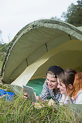 Young couple using digital tablet in camp tent, Bavaria, Germany