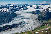 """Seen from the air, Riggs Glacier drains into the fjord of Muir Inlet in the East Arm of Glacier Bay National Park, in Alaska, USA. Flightseeing from Skagway or Haines is a spectacular way to see Glacier Bay. We were bedazzled by Mountain Flying Service's 1.3-hour West Arm tour from Skagway. Glacier Bay is honored by UNESCO as part of a huge Biosphere Reserve and World Heritage site shared between Canada and the United States. In 1750-80, Glacier Bay was totally covered by ice, which has since radically melted away. In 1794, Captain George Vancover found Icy Strait on the Gulf of Alaska choked with ice, and all but a 3-mile indentation of Glacier Bay was filled by a huge tongue of the Grand Pacific Glacier, 4000 feet deep and 20 miles wide. By 1879, naturalist John Muir reported that the ice had retreated 48 miles up the bay. In 1890, """"Glacier Bay"""" was named by Captain Beardslee of the U.S. Navy. Over the last 200 years, melting glaciers have exposed 65 miles of ocean. As of 2019, glaciers cover only 27% of the Park area. Since the mid 1900s, Alaska has warmed 3 degrees Fahrenheit and its winters have warmed nearly 6 degrees. Human-caused climate change induced by emissions of greenhouse gases continues to accelerate warming at an unprecedented rate. Climate change is having disproportionate effects in the Arctic, which is heating up twice as fast as the rest of Earth."""