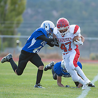 Pine Hill running back Maynard Alonzo (47) is pushed out of bounds by Warriors defender Tyren Wheeler (44), in Navajo on Saturday.