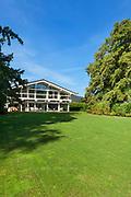 Facade of a beautiful house with green garden, summer day