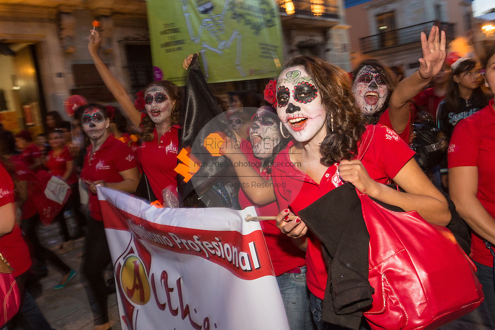 A group of woman wearing skeleton face paint parade during the Day of the Dead Festival known in spanish as Día de Muertos October 30, 2014 in Oaxaca, Mexico.
