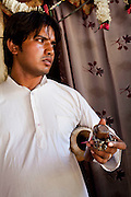 """Sanjay Kumar, 22, a former snake charmer, holds his snake charming musical instruments, that he now uses in cultural performances (without the snakes), at his home in Naraina gaon, Titana village, Samalkha town, Haryana, India on 15th June 2012. """"Only during elections does the government pay attention to us,"""" he says. India's snake charmer communities suffer from a loss of livelihood because of stringent wildlife laws and are forced to resort to begging or working as daily wage labourers. A new program to encourage the snake charmer's children to attend school is underway, to keep them from becoming daily-wage child labourers or joining their parents in scavenging and begging in cities. Photo by Suzanne Lee for The National"""