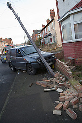 Scene of a road traffic accident; vehicle crashed into a telegraph pole and garden wall,