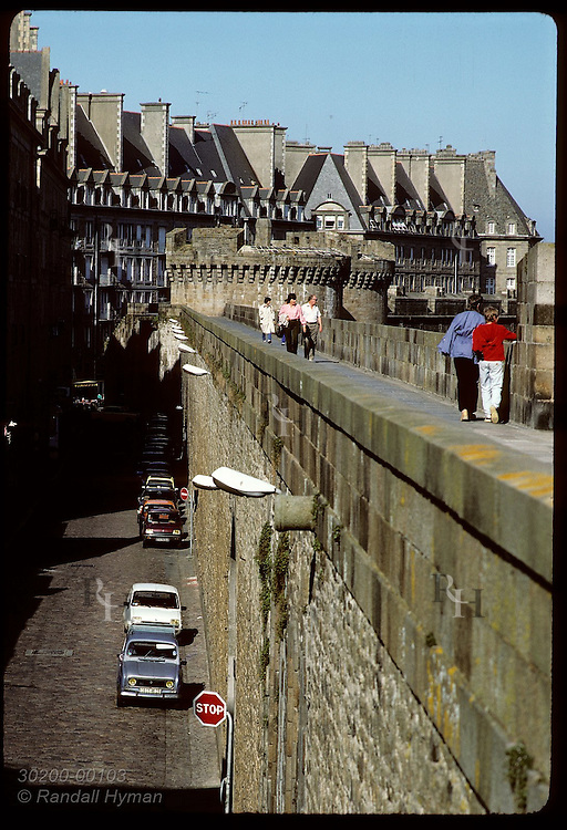 Tourists walk along the battlements of fortress city of Saint Malo far above stone street. France