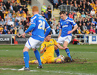 Portsmouth's Jed Wallace is tackled by Newport County's Andrew Hughes (partially obscured)<br /> <br /> Photo by Kevin Barnes/CameraSport<br /> <br /> Football - The Football League Sky Bet League Two - Newport County AFC v Portsmouth - Saturday 29th March 2014 - Rodney Parade - Newport<br /> <br /> © CameraSport - 43 Linden Ave. Countesthorpe. Leicester. England. LE8 5PG - Tel: +44 (0) 116 277 4147 - admin@camerasport.com - www.camerasport.com
