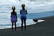 Two Australian tourist children (5 years old and 9 years old) watching a dog on a black sand beach. Near Goa Lawah Temple, Bali, Indonesia.