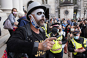 Compere leads the Walk of Shame disruptive mach through the City of London by environmental group Extinction Rebellion as police try to move the protest, on 4th September 2020 in London, United Kingdom. The walk visited various locations in the financial district, to protest against companies and institutions with historical links to the slave trade, or who finance or insure projects which are seen as ecologically unsound. The message by the group is that 'apologies and token attempts at diversity are not enough to address this legacy and present reality. Our demand is reparations and reparatory justice for those affected by colonial and neo-colonial exploitation'. Extinction Rebellion is a climate change group started in 2018 and has gained a huge following of people committed to peaceful protests. These protests are highlighting that the government is not doing enough to avoid catastrophic climate change and to demand the government take radical action to save the planet.