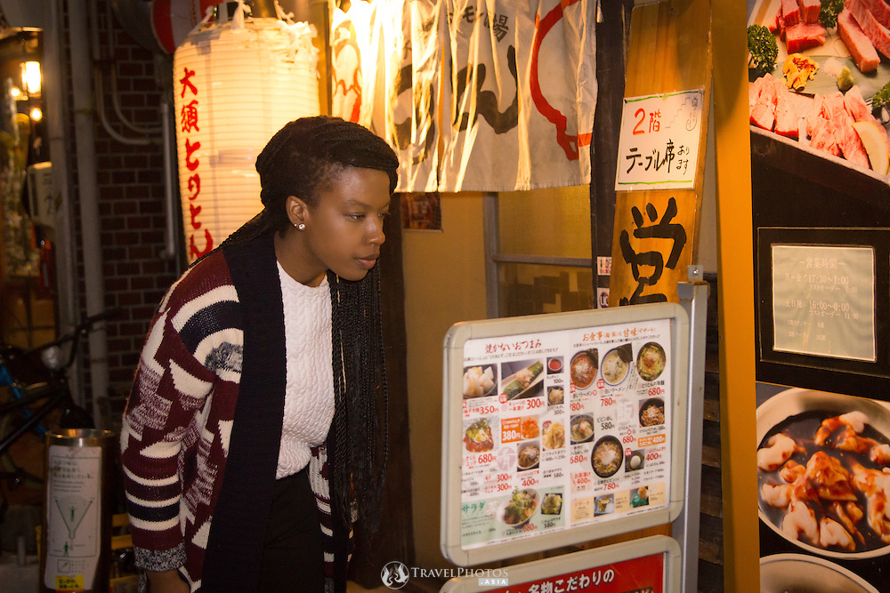 A young lady travelling in Japan looking at a restaurant menu in the evening.