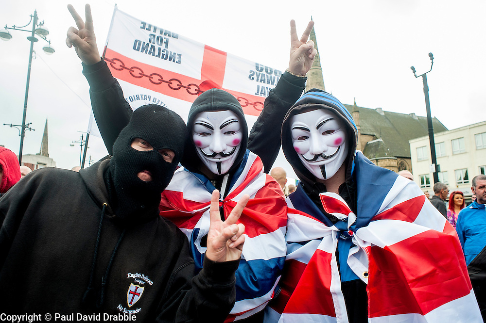 """Rotherham England<br /> 13 September 2014 <br /> Protestors wearing Anonymous masks and Union Flags with EDL supporters outside Rotherham Town Hall before the start of the English Defence Leagues Justice for the Rotherham 1400 March on Saturday Afternoon described by an EDL Facebook Page as """"a protest against the Pakistani Muslim grooming gangs"""" on Saturday Afternoon <br /> <br /> <br /> Image © Paul David Drabble <br /> www.pauldaviddrabble.co.uk"""
