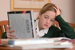 10 year old schoolgirl doing science homework looking worried or having difficulty UK