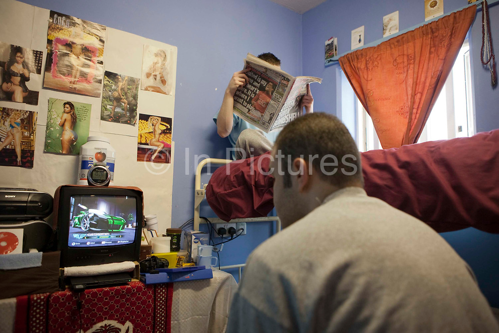 An 'Enhanced' prisoner reading a newspaper while his cell mate plays computer games on H wing at the Young Offenders Institution in Aylesbury, United Kingdom. Under the Incentives and Earned Privilege Scheme, prisoners in the UK can earn extra privileges for good behaviour such as wearing their own clothes, having televisions in their cells, and having more free time to socialise. They are often housed together in their own wing. There are three levels of earned privileges - Basic, Standard and Enhanced. HMYOI / HM Prison Aylesbury (Her Majesty's Young Offender Institution Aylesbury) is a prison is operated by Her Majesty's Prison Service.