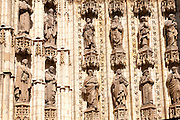 Detail of carved stonework of cathedral frontage showing statues of saints, Seville, Spain