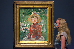 """© Licensed to London News Pictures. 04/08/2020. LONDON, UK. A staff member poses with """"Young Girl on the Grass, the Red Bodice (Mademoiselle Isabelle Lambert"""", 1895, by Berthe Morisot. Preview of """"Gauguin and the Impressionists : Masterpieces from the Ordrupgaard Collection"""" at the Royal Academy of Arts in Piccadilly.  60 works from a collection of Impressionist paintings, assembled by wealthy Danish couple Wilhelm and Henny Hansen, are on show 7 August to 18 October 2020, and includes masterpieces by Gauguin, Degas, Monet, Morisot, Pissarro, Renoir and Sisley.  Photo credit: Stephen Chung/LNP"""