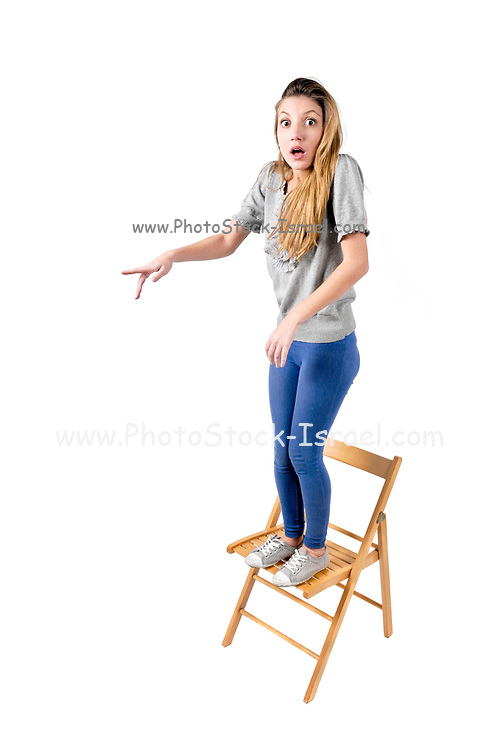 Frightened Young teen girl stands on a chair pointing at the threat (not depicted)