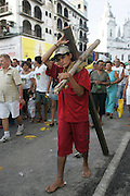 Barefoot, a young man walks the procession's 5 km across the city of Belem do Para. The cross is made out of massive wood.