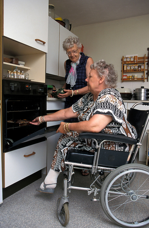 Woman in wheelchair cooking her meal in purpose built  accommodation with low level oven,
