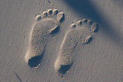 The imprint of two left footprints in the sand on a bea
