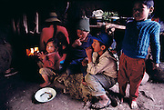 Children of the Ochoas family waiting while their mother, Bernadina, prepares a breakfast treat of roasted waykjuiro worms, Chinchapujio, Peru. (Man Eating Bugs page 154 Top)